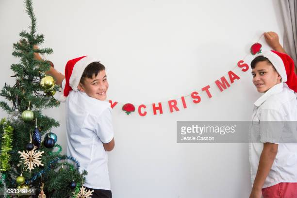 Twins putting Christmas decoration up on wall