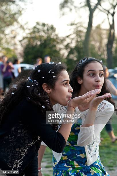 Twins Rama and Elana El Agha of Fairfax, Virginia, play with cherry blossom petals in Washington on March 23, 2012. The National Cherry Blossom...