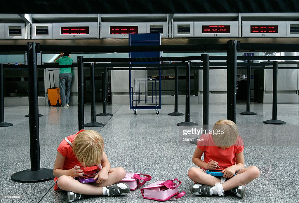 Twins Sarah Mattsson (L) and Emma Mattsson, 6, of San Jose, California keep themselves busy at an empty ticket counter as their parents try and figure out if they will be able to fly out at San Francisco International Airport on July 6, 2013 in San Francisco, California. A Boeing 777 Asiana Airlines passenger aircraft coming from Seoul, South Korea crashed while landing. Two fatalities have so far been reported.