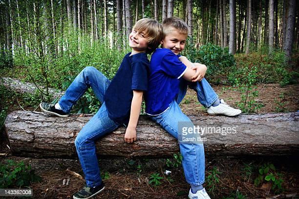 Twins sitting on tree trunk
