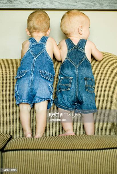 Twins standing on a sofa together