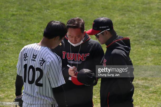 LG Twins team staff write Corona 19 Out on their cap ahead of their intrateam game to be broadcasted online for their fans at a empty Jamshil...