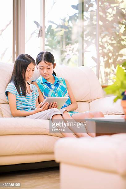 twins using digital tablets - leren stock pictures, royalty-free photos & images