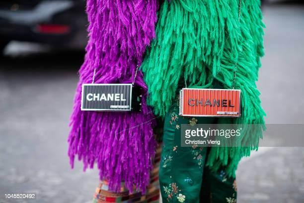 Twins wearing green and purple fake fur jacket and red and black Chanel bag is seen outside Chanel during Paris Fashion Week Womenswear Spring/Summer...