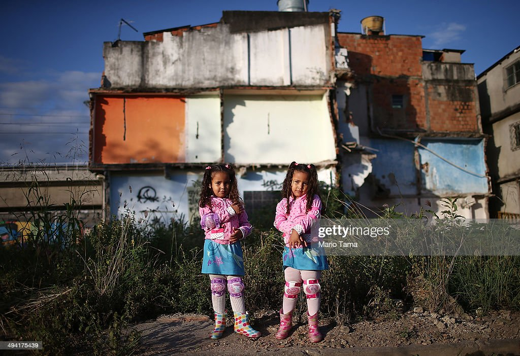 Twins Wendy (R) and Isis Guimaraes pose in front of their home which remains standing in an area where homes were torn down in the Manguinhos community on May 27, 2014 in Rio de Janiero, Brazil. The twins' father says they have been made sick from open sewage in the area. Residents from one section of the 'favela', visited by Pope Francis in July 2013, have been affected by construction from the improvement works project begun in 2008. A full sanitation system has yet to be built. Evictions and demolitions have been occurring in Rio favelas ahead of the 2014 FIFA World Cup and Rio 2016 Olympic Games in spite of a housing shortage in the city. Rio's housing and urban planning goals include a planned five percent reduction of areas occupied by favelas by 2016. Alternative affordable housing, generally on the peripheries of the city, is unable to meet demand and some residents complain they have not received adequate compensation for demolished homes.