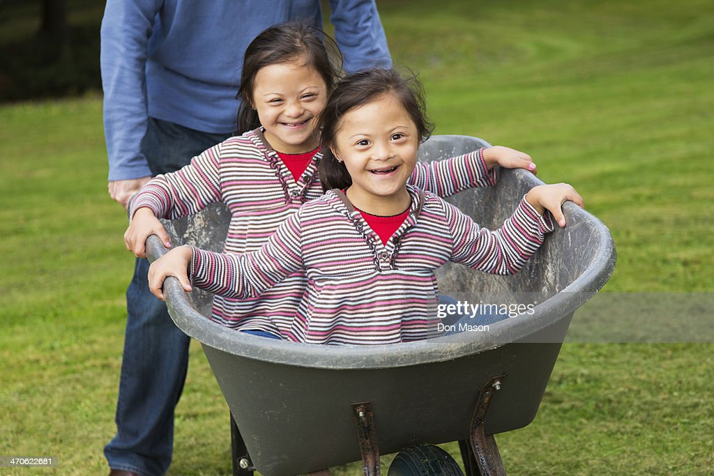 Twins with Down's Syndrome smiling in wheelbarrow : Stock Photo
