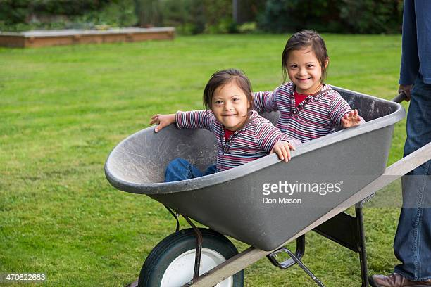 twins with down's syndrome smiling in wheelbarrow - asian twins stock photos and pictures