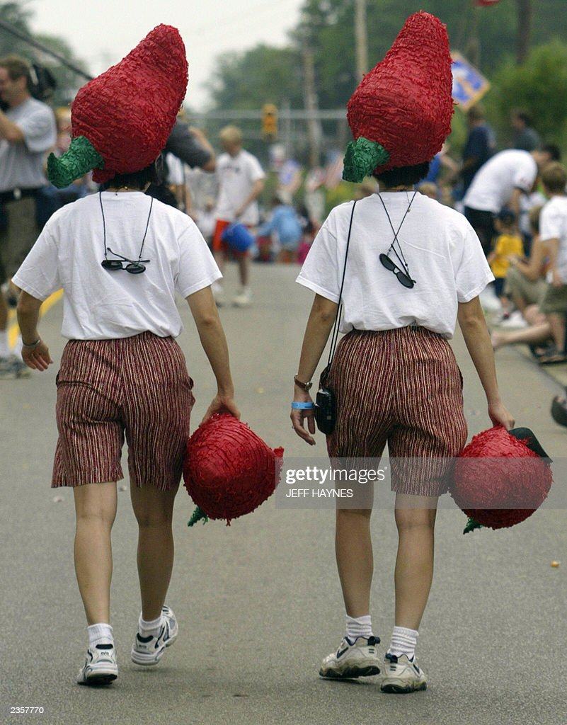 Twins Zim (L) and Kieu (R) Pham walk the parade route during the 28th Twins Day Festival parade 02 August, 2003 in Twinsburg, Ohio. The event, billed as the 'Largest Annual Gathering of Twins in the World,' is the only festival where twins worldwide gather to celebrate being of multiple birth. AFP PHOTO/Jeff HAYNES