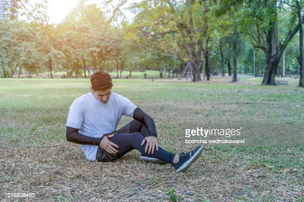 twisted ankle. young runner touching his sprained leg - knee stock pictures, royalty-free photos & images