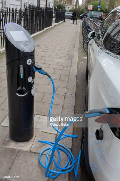 A twisted blue electric recharging cable is plugged in to a white car on a central London street on 16th April 2018 in London England