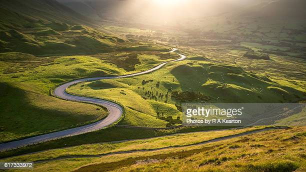 Twisty road leading into a sunlit country landscape
