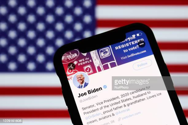 Twitter feed of candidate for President of the USA Joe Biden is seen displayed on a phone screen with American flag in the background in this...