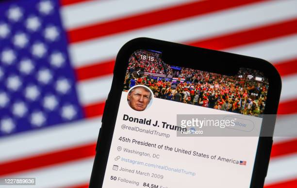 Twitter feed of the President of the USA Donald Trump is seen displayed on a phone screen with American flag in the background in this illustration...