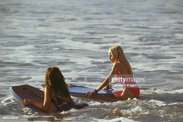 Two 10 Year Old Girls BoogieBoarding In The Pacific Ocean