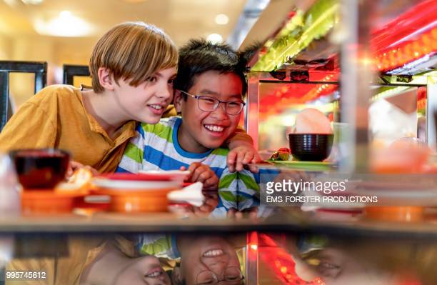 two 10 years old boys in sushi restaurant - sushi restaurant stock photos and pictures