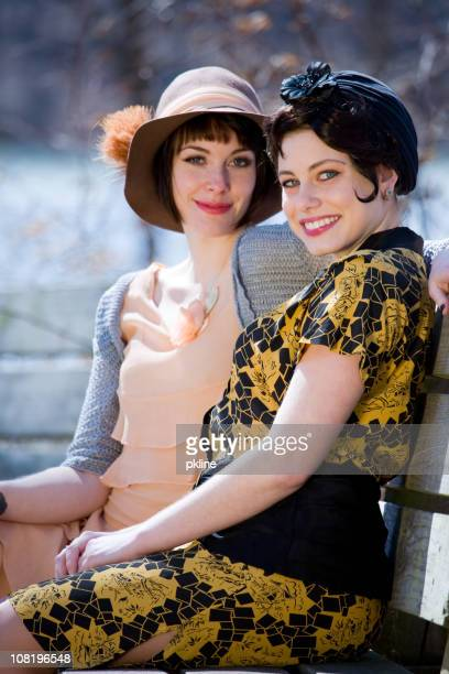 Two 1920s style ladies sit on a bench
