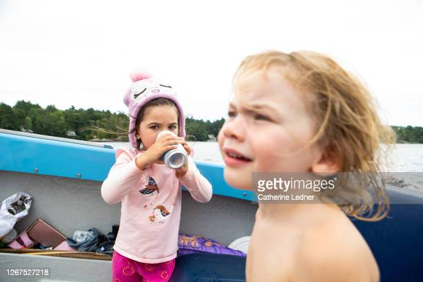 two 3 year old girls on motorboat on a maine lake on an overcast day.  one girl is drinking water from a can. - catherine ledner stock pictures, royalty-free photos & images