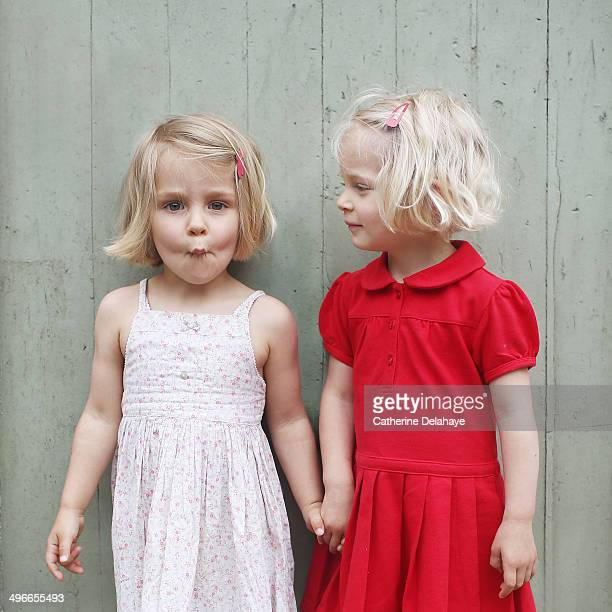 Two 3 years old twins girls posing together