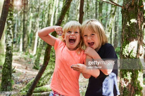 two 4 year old children playing together in forest - children only stock pictures, royalty-free photos & images