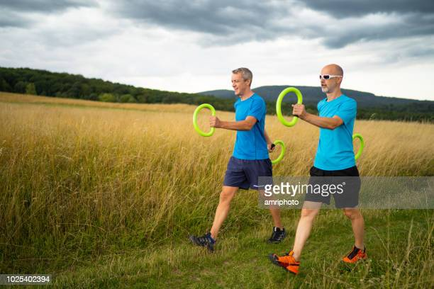 two 45 years old men walking with smoveys sports outdoor training