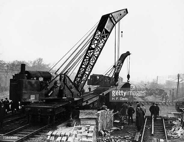Two 50ton railmounted cranes lifting the main girders into position during construction of a new bridge over Thorpes Road on the LMS line between...