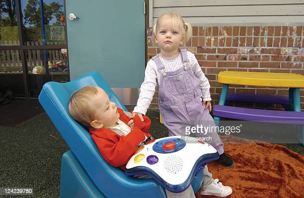 two absolutely adorable children, one with disabilities, one without, playing together at school. - cerebrum stock pictures, royalty-free photos & images