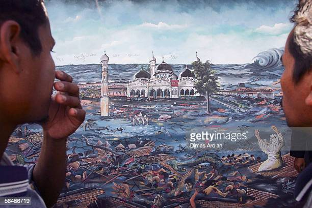 Two Acehnese men and tsunami survivors stands in front of a painting depicting the tsunsmi disaster that hit the area one year ago on December 25...