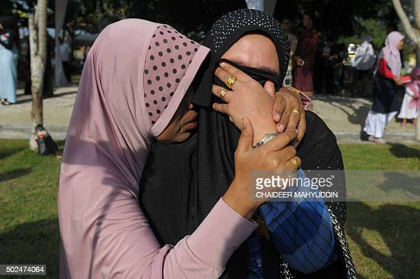 TOPSHOT Two Acehnese women grieve at the Ulhee Lheue mass cemetery where thousands of the 2004 tsunami victims are buried in Banda Aceh on December...