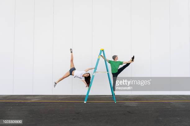 two acrobats doing tricks on a ladder - 離れ技 ストックフォトと画像