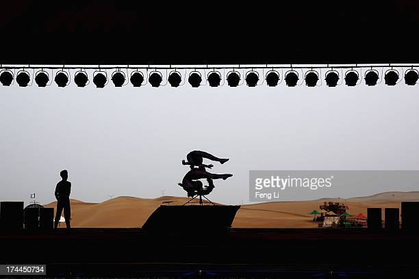 Two acrobats perform in Xiangshawan Desert also called Sounding Sand Desert on July 21 2013 in Ordos of Inner Mongolia Autonomous Region China...