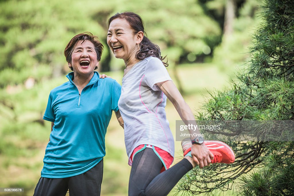Two active Japanese women laughing, one stretching leg : Stock Photo