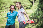 Two active Japanese women laughing, one stretching leg