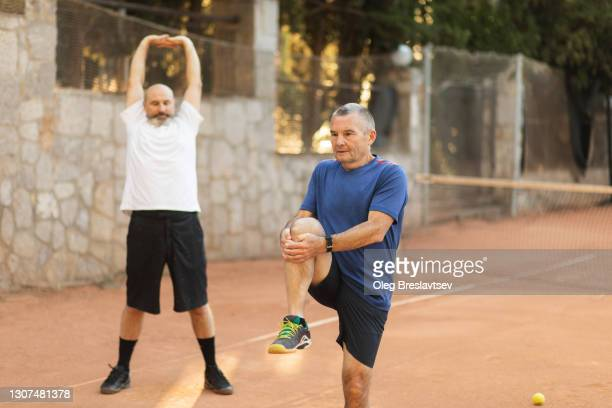two active senior friends warming up, stretching and exercising before tennis game. healthy lifestyle of old people - warming up stock pictures, royalty-free photos & images