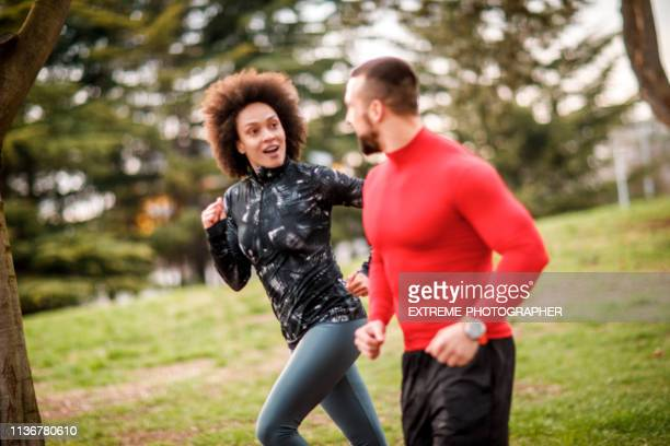 two active young athletes doing a running exercise together on an all-weather running track in a city park - all weather running track stock pictures, royalty-free photos & images
