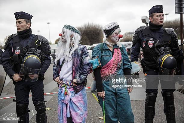 Two activists perform beside the police as they attend a demonstration near the Arc de Triomphe at the Avenue de la Grande Armee boulevard on...