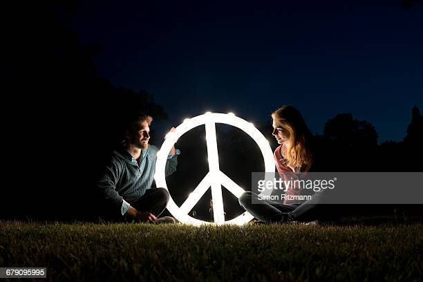 Two activists with illuminated peace sign at night