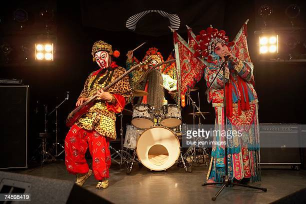 two actors and an actress dressed as traditional beijing opera characters play rock and roll together on stage. - masked musicians stock-fotos und bilder