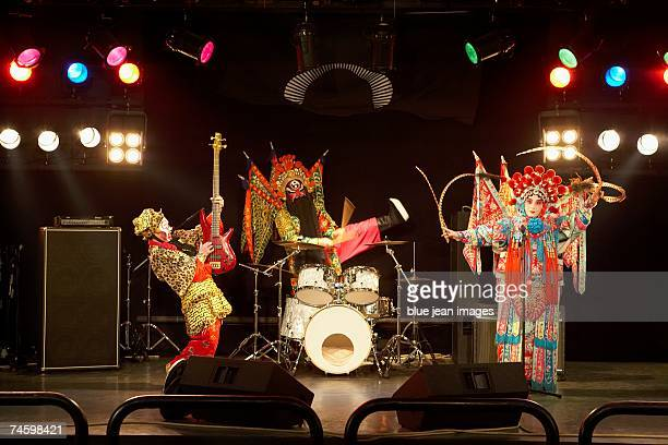 two actors and an actress dressed as traditional beijing opera characters play rock and roll together on stage. - beijing opera stock photos and pictures