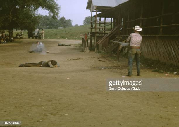 """Two actors wearing cowboy costumes perform a re-enactment of a """"wild west"""" gunfight, 1965."""