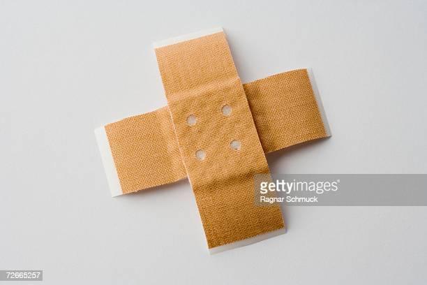 two adhesive bandages in cross shape - esparadrapo fotografías e imágenes de stock