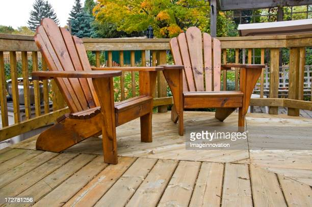 Two Adirondack chairs on a backyard wood deck