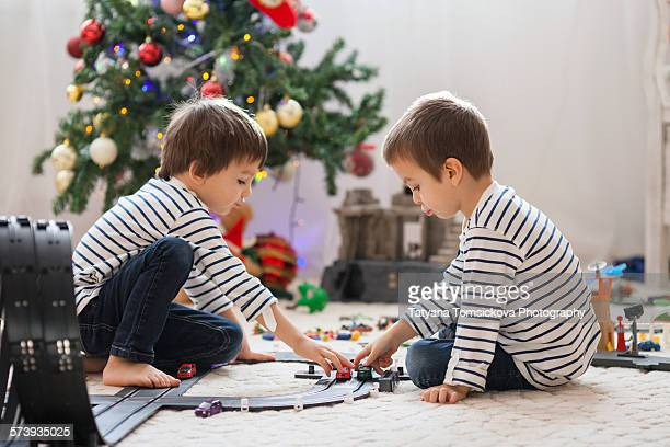 Two adorable boys, playing with toys on Christmas