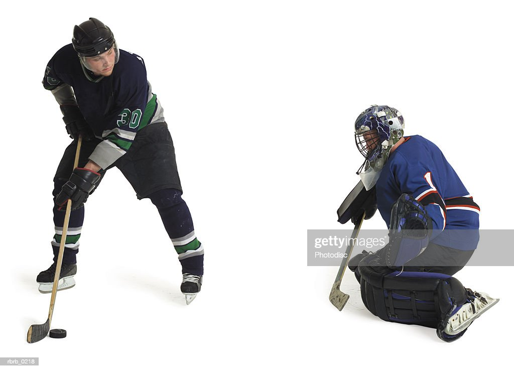two adult caucasian male hockey players from opposing teams play as one prepares to shoot and goalie crouches and blocks : Stockfoto