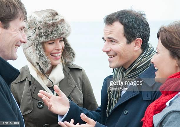 Two adult couples talking on beach, Thurlestone, Devon, UK