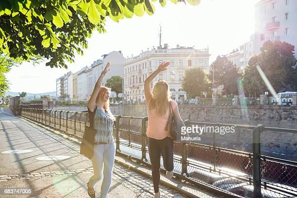 Two adult female friends dancing on sidewalk, Vienna, Austria
