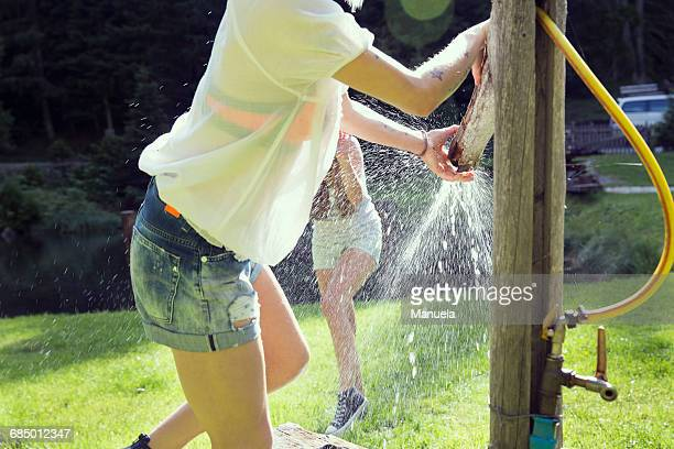 two adult female friends play fighting sprinkling water hose in garden - women in wet t shirts stock pictures, royalty-free photos & images
