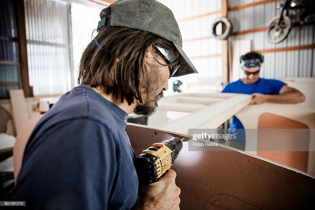 Two adult, male carpenters working with tools in a wood shop : Stock Photo
