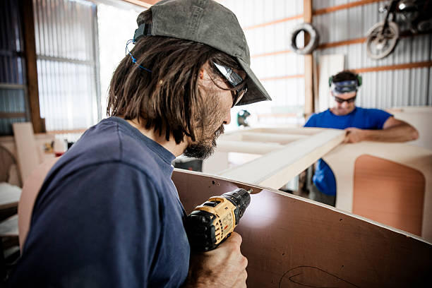 Two adult, male carpenters working with tools in a wood shop