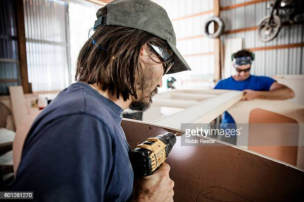 two adult, male carpenters working with tools in a wood shop - robb reece stock photos and pictures