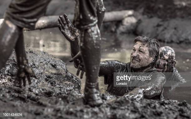 two adult male team mates having sporty fun at a public mud run obstacle course - obstacle course stock photos and pictures